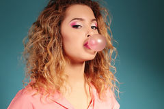 Beautiful young girl with blond hair and evening makeup with bubble gum Royalty Free Stock Photo