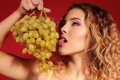 Beautiful young girl with blond hair and evening makeup with grapes Stock Photos