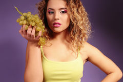 Beautiful young girl with blond hair and evening makeup with grapes Royalty Free Stock Photos