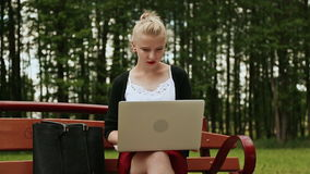Beautiful young girl with blond hair on a park bench working on her laptop. Girl using laptop, typing. Front view. stock video footage
