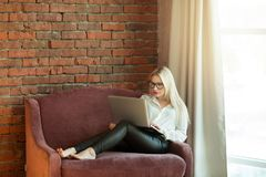 Beautiful young girl with blond hair sitting. On the couch with a laptop in hand near a brick wall Royalty Free Stock Photos