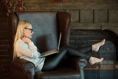 Beautiful young girl with blond hair sitting. In a chair with a laptop in hand near the fireplace Stock Image