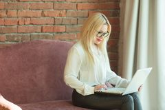 Beautiful young girl with blond hair sitting. On the couch with a laptop in hand near a brick wall Stock Photography