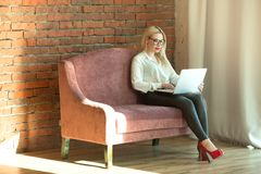 Beautiful young girl with blond hair sitting. On the couch with a laptop in hand near a brick wall Stock Photo