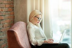 Beautiful young girl with blond hair sitting. On the couch with a laptop in hand near a brick wall Stock Images