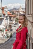 Beautiful young girl blonde in a red coat, stands on the background of the city of Tbilisi. royalty free stock photography