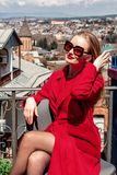 A beautiful young girl blonde in sunglasses and a red coat, stands on the background of the city of Tbilisi. stock photography