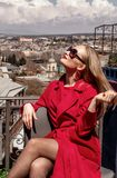 A beautiful young girl blonde in sunglasses and a red coat, stands on the background of the city of Tbilisi. stock photo