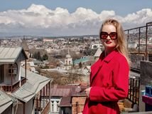 A beautiful young girl blonde in sunglasses and a red coat, stands on the background of the city of Tbilisi. royalty free stock images