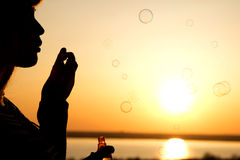 Beautiful young girl blow bubbles on nature Royalty Free Stock Photography