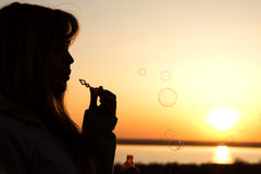 Beautiful young girl blow bubbles on nature Stock Image