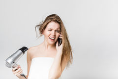 Beautiful young girl blow drying her hair while talking on the s. Portrait of a beautiful young girl blow drying her hair while talking on the smartphone Royalty Free Stock Photo