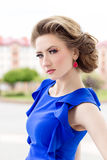 Beautiful young girl in a blue dress with a beautiful hairstyle and makeup stands on street in town Royalty Free Stock Photo