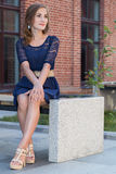 Beautiful young girl in blue dress. Is sitting Royalty Free Stock Images