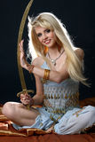 Beautiful young girl in blue east dress. Beautiful sexy blonde in blue east dress with a sword on dark background Stock Photography