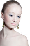Beautiful young girl with blue eyes, isolated. Beautiful young woman with blue eyes and green golden earrings isolated on white stock photo