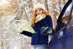 Beautiful young girl in blue jacket standing near a car, holding map in hand and drinking tea. Travel girl. Royalty Free Stock Photo
