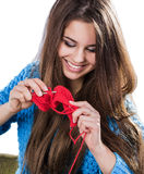 Beautiful young girl in a blue sweater standing with a red ball of yarn and knitting a scarf and Spitz. Smiles. White background. Royalty Free Stock Images