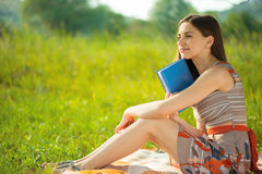 Beautiful young girl with book at wonderful green meadow Stock Photo