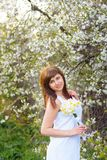 Beautiful young girl with a bouquet of daffodils in a white dress on a background of cherry blossoms stock image