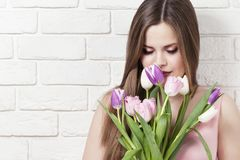 Beautiful young girl with a bouquet of tulips. Portrait. Flowers in the hands of the girl. Stock Photo