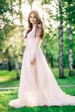 Beautiful young girl bride brunette in delicate Bridal boudoir gown of lace and tulle in beige color is outdoors,. In a Park with trees, birches Royalty Free Stock Photo