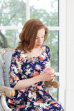 A beautiful young girl in a bright colorful dress sits in an armchair by the window and looks thoughtfully at the rose Stock Image