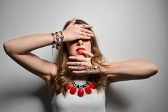 Beautiful young girl with bright lips in the studio. Jewelry costume jewelry - earrings, bracelet, red necklace. stock photo