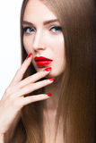Beautiful young girl with a bright  make-up and red nails. Royalty Free Stock Image