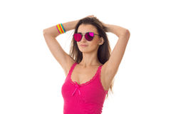 Beautiful young girl in a bright pink shirt and glasses raised her hands up Royalty Free Stock Photo