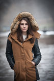 Beautiful young girl with brown coat trimmed with gray fur enjoying the winter scenery in park. Teenage girl with black leather. Sleeves coat posing in winter Royalty Free Stock Photos