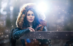 Beautiful young girl with brown fur cape enjoying the winter scenery sitting on the bench in park. Teenage girl posing, winter Stock Photo