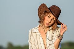 Beautiful young girl with brown golden curls hair in a cowboy hat looking and posing on the blue sky background stock photo