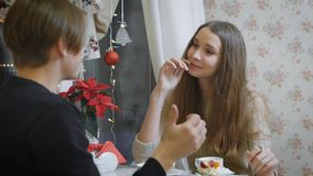 Beautiful young girl with brown hair sitting in a youth cafe with a teen man trying a delicious dessert with a spoon. Beautiful young girl with long hair sitting stock footage