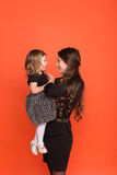 Beautiful young girl in a business suit and little girl in a bla Stock Photography