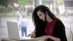 Beautiful young girl in a business suit looking for a job fill out a form or resume looking at the laptop sit in a cafe. concept e stock footage