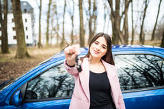 Beautiful young girl with car key in hand in front of her new car on road. Stock Photo