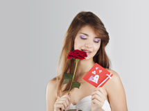 Beautiful young girl with a card. And a rose in his hand on a white background stock image