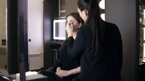 Beautiful young girl in casual black dress sitting on the chair in front the mirror while female makeup master applying. Cosmetics on her face using a brush stock footage