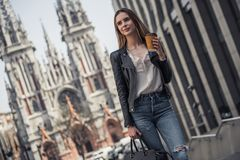 Girl in city. Beautiful young girl in casual clothes is holding cup of coffee and smiling while walking in the city center royalty free stock photos