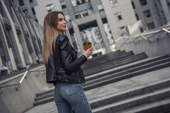 Girl in city. Beautiful young girl in casual clothes is holding cup of coffee and smiling while walking in the city center stock photos