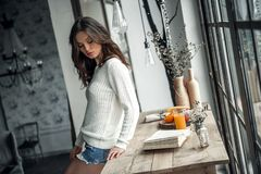 Girl at home. Beautiful young girl in casual clothes is looking away while leaning on wooden table at home Royalty Free Stock Images