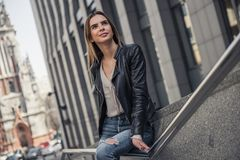 Girl in city. Beautiful young girl in casual clothes is looking away and smiling while resting in the city center royalty free stock images