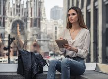 Girl in city. Beautiful young girl in casual clothes is making notes and looking away while resting in city center royalty free stock images