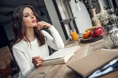 Girl at home. Beautiful young girl in casual clothes is reading a book and looking out the window while sitting at the wooden table at home Royalty Free Stock Photos