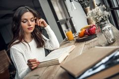 Girl at home. Beautiful young girl in casual clothes is reading a book while sitting at the wooden table at home Stock Image