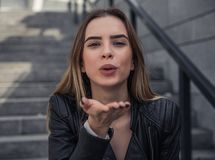 Girl in city. Beautiful young girl in casual clothes is sending air kiss at camera and smiling while walking in the city royalty free stock image