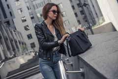 Girl in city. Beautiful young girl in casual clothes and sun glasses is looking for something in her bag while walking in the city center royalty free stock photography