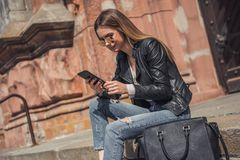 Girl in city. Beautiful young girl in casual clothes and sun glasses is using a smart phone and smiling while resting in the city center royalty free stock image
