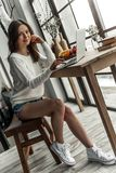 Girl at home. Beautiful young girl in casual clothes is working with a laptop, looking at camera and smiling while sitting at the wooden table at home Royalty Free Stock Photo